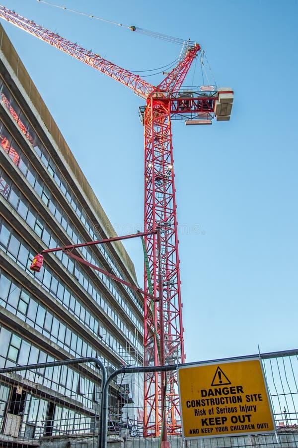 危险建造场所把与红色起重机的标志关在外面在城市 免版税库存照片