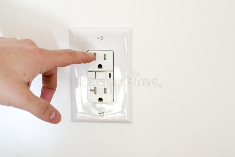 危险手指接近电子插口 免版税库存图片