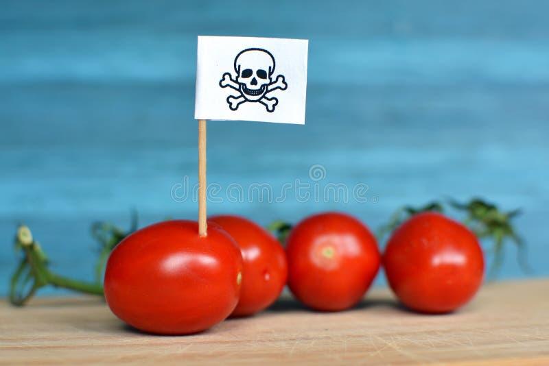 危险杀虫剂用法的概念在农业食品的用红色蕃茄和毒性警告 免版税库存图片