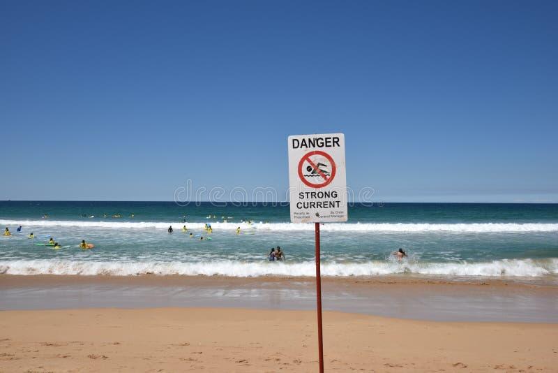 危险标志、冲浪者和其他人民有好时间在著名男子气概的海滩在悉尼,澳大利亚 免版税图库摄影