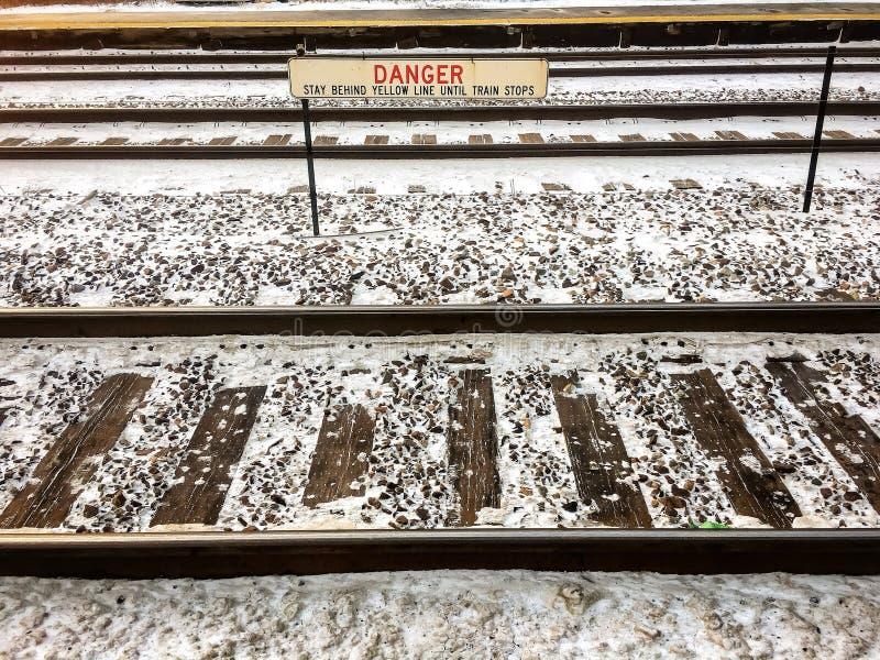 危险标志盘旋在积雪的火车轨道 图库摄影