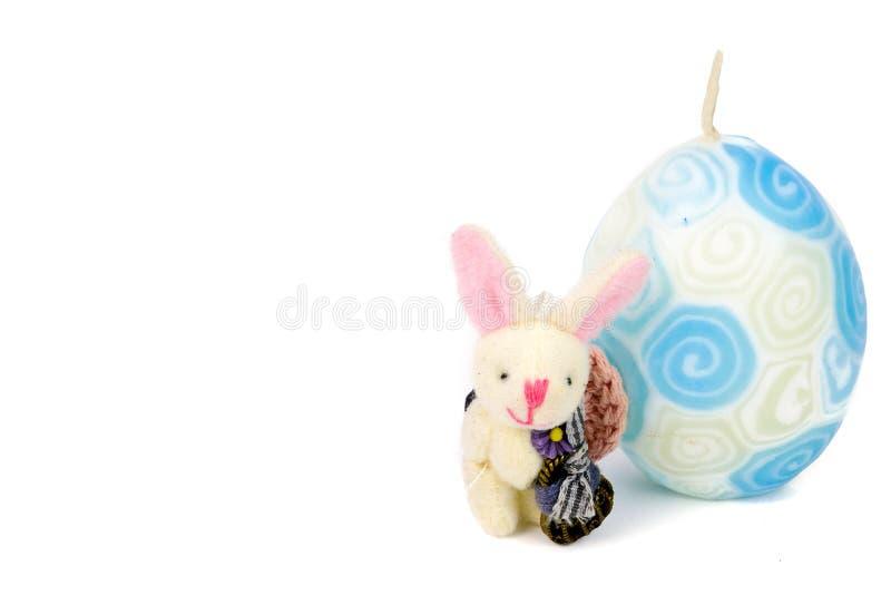 即逗人喜爱的矮小的手工制造兔宝宝和一个白色和蓝色复活节蜡烛 库存照片