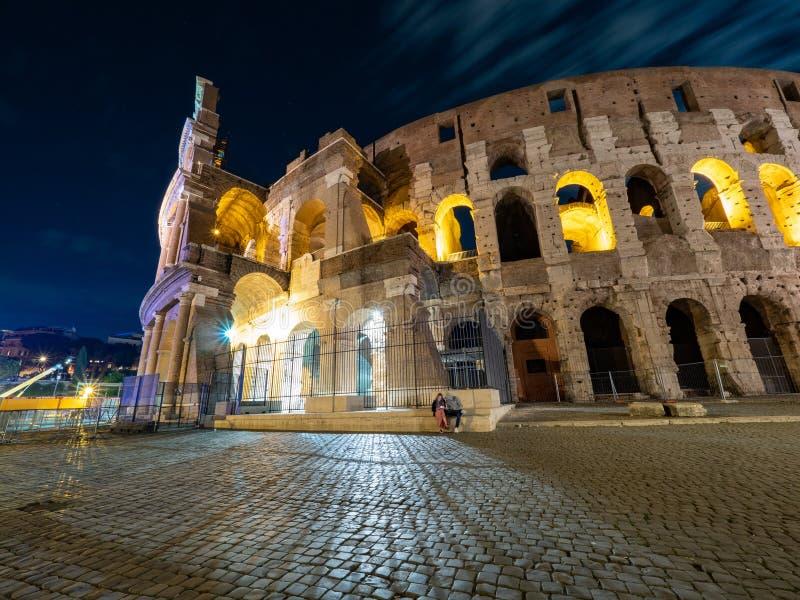 卵形圆形露天剧场的夜间图片在罗马,有轻和满月的意大利的中心  库存照片