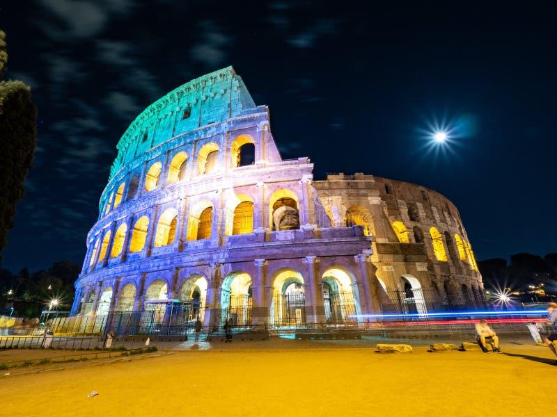 卵形圆形露天剧场的夜间图片在罗马,有轻和满月的意大利的中心  免版税库存图片