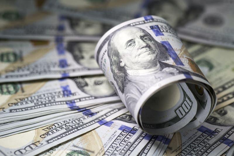 卷一百在美金背景的美元票据 库存照片