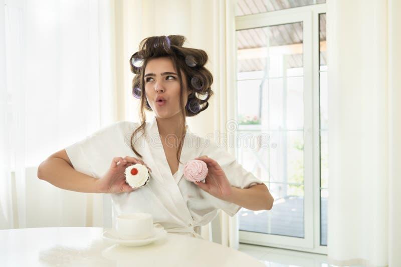 卷发夹的美丽的滑稽的年轻深色的妇女在两只手中的拿着两块杯形蛋糕在她的坐与杯子的乳房附近 免版税库存图片