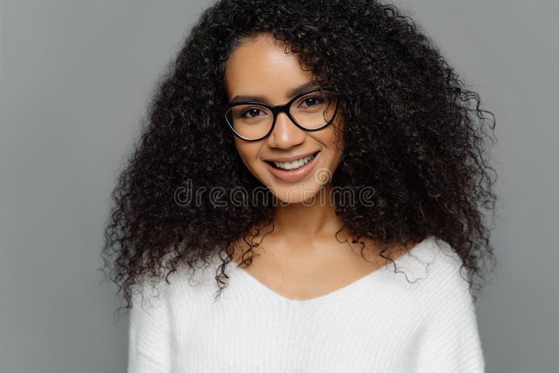卷发的微笑的妇女特写有健康黑暗的皮肤,蓬松卷发发型,对照相机,weras光学玻璃轻轻地微笑和 库存照片