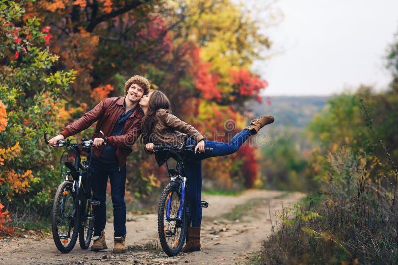 卷发的长着大髭须的人和一个矿石头发的女孩在秋天站立与自行车在路并且显示快乐的情感 图库摄影
