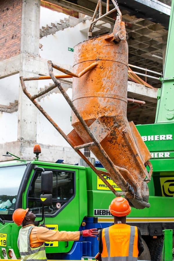 卷扬在工地工作的水泥搅拌车的建筑工人 图库摄影