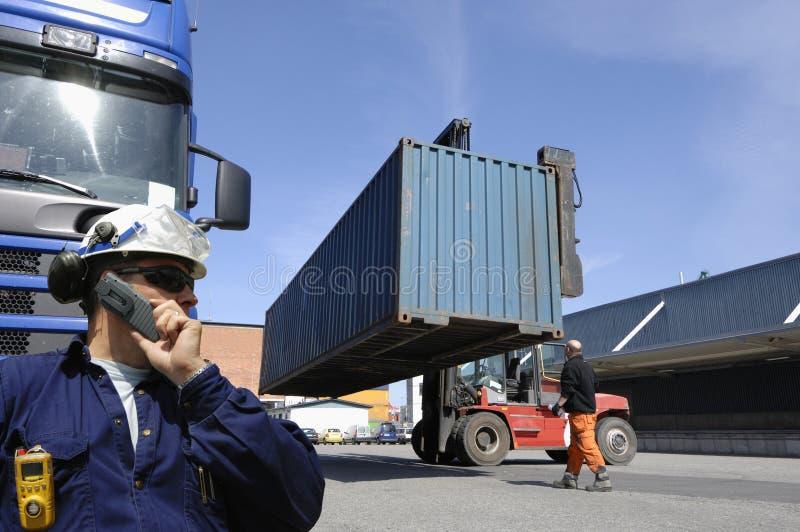 卷扬货物和发运集装箱的铲车 免版税库存照片