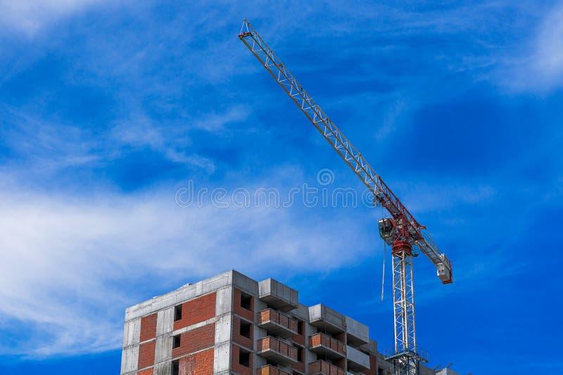 卷扬运转在蓝色多云天空的楼房建筑的起重机 免版税库存照片