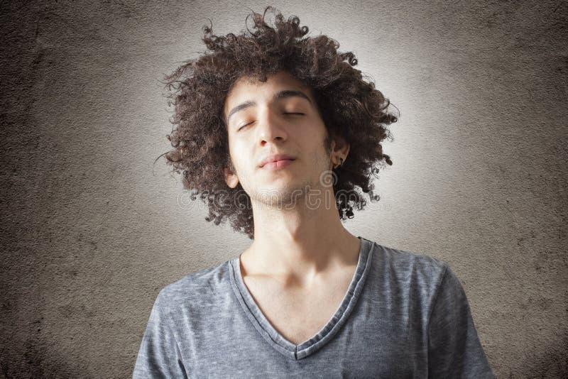 年轻卷曲人面孔画象与眼睛的关闭了 免版税库存照片