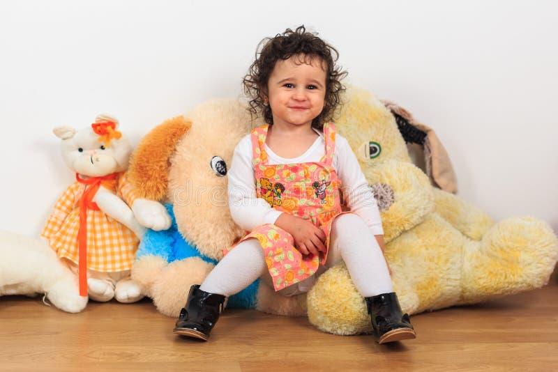 卷曲女婴微笑和坐长毛绒狗玩具 免版税图库摄影