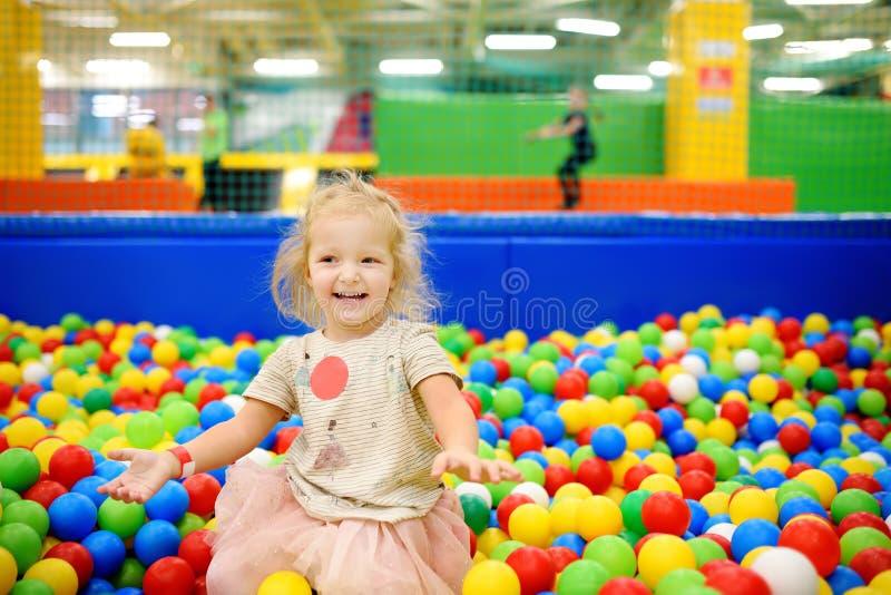 卷曲小女孩获得乐趣在与五颜六色的球的球坑 免版税库存照片