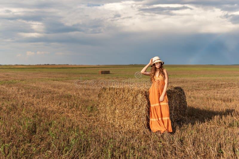卷曲年轻农村少年女孩在捆绑在的干草附近站立sundress和帽子在一块被收获的麦田与a背景  免版税库存图片