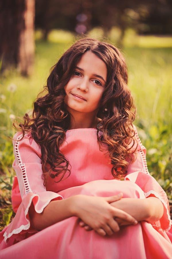 卷曲微笑的儿童女孩夏天画象童话公主礼服的在森林里 库存图片