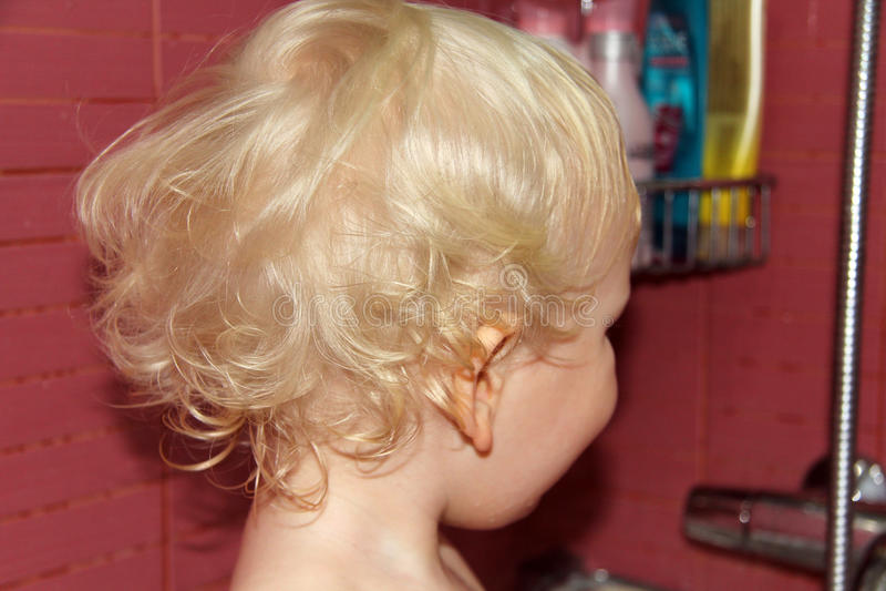卷曲波浪发白肤金发的婴孩boyб后面 免版税库存照片