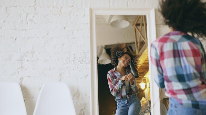 卷曲滑稽的非裔美国人的女孩跳舞和在家唱歌与在镜子前面的吹风器 免版税图库摄影