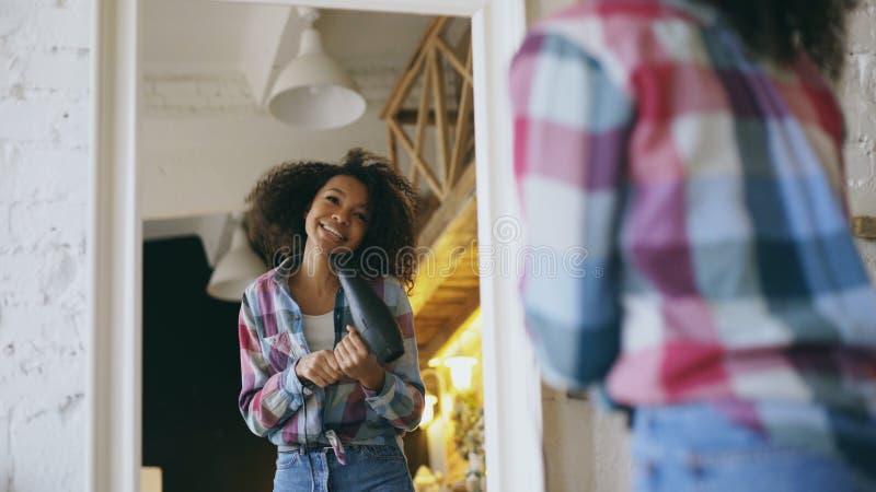 卷曲滑稽的非裔美国人的女孩跳舞和在家唱歌与在镜子前面的吹风器 库存图片