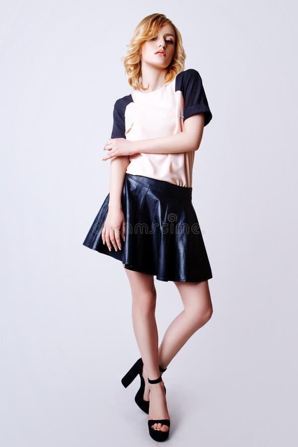 年轻卷曲白肤金发的妇女演播室照片白色背景的 免版税图库摄影