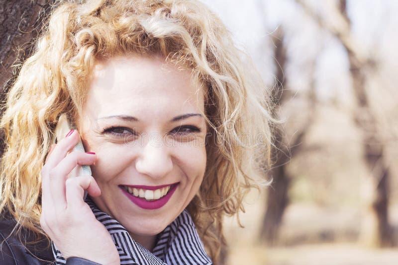 年轻卷曲白肤金发的妇女谈话在电话户外 库存图片