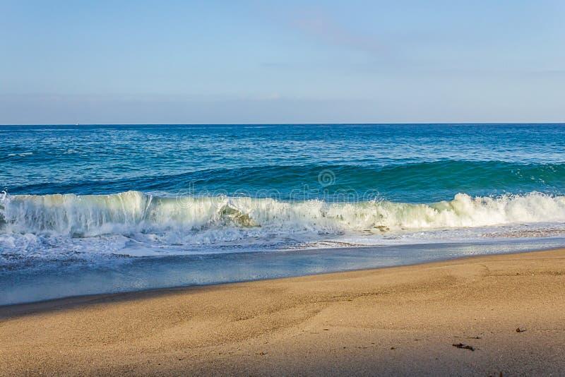 卷曲的碎波管,起泡沫与回流,与近来膨胀,在含沙岸 免版税库存照片