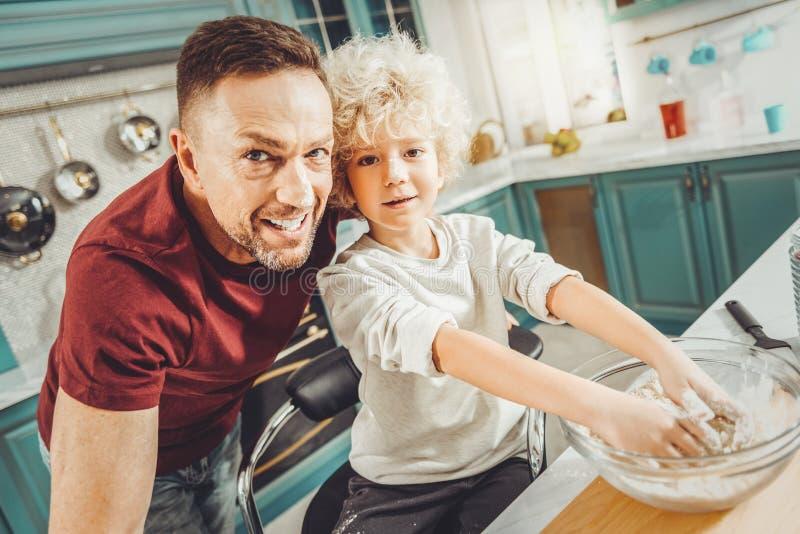 卷曲逗人喜爱的饼的男孩揉的面团与父母引导 免版税库存照片
