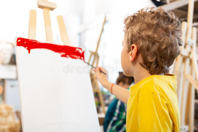 卷曲金发的与红色的男孩上色纸 图库摄影