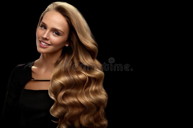 卷曲金发 与华美的容量头发的秀丽模型 免版税库存图片