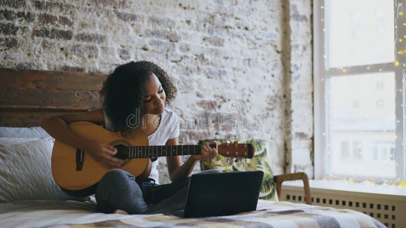卷曲非裔美国人的少年女孩concentraing的学会弹吉他使用便携式计算机在家坐床 库存图片