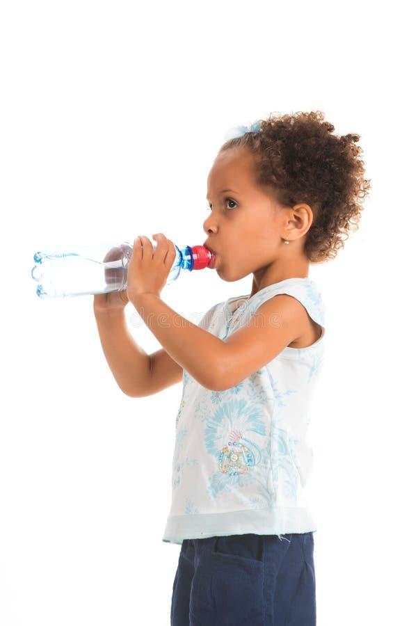 卷曲非洲女孩喝从一个瓶的水,在白色背景 免版税库存图片