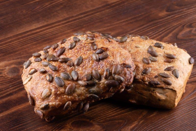 卷添面包与在木背景的南瓜籽 免版税库存图片