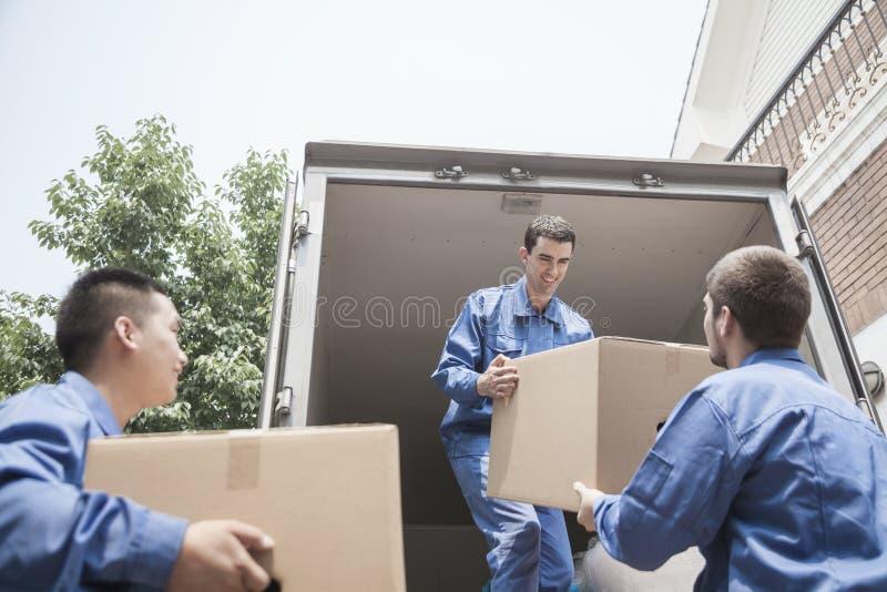 卸载一辆移动货车的搬家工人,通过纸板箱 免版税库存图片