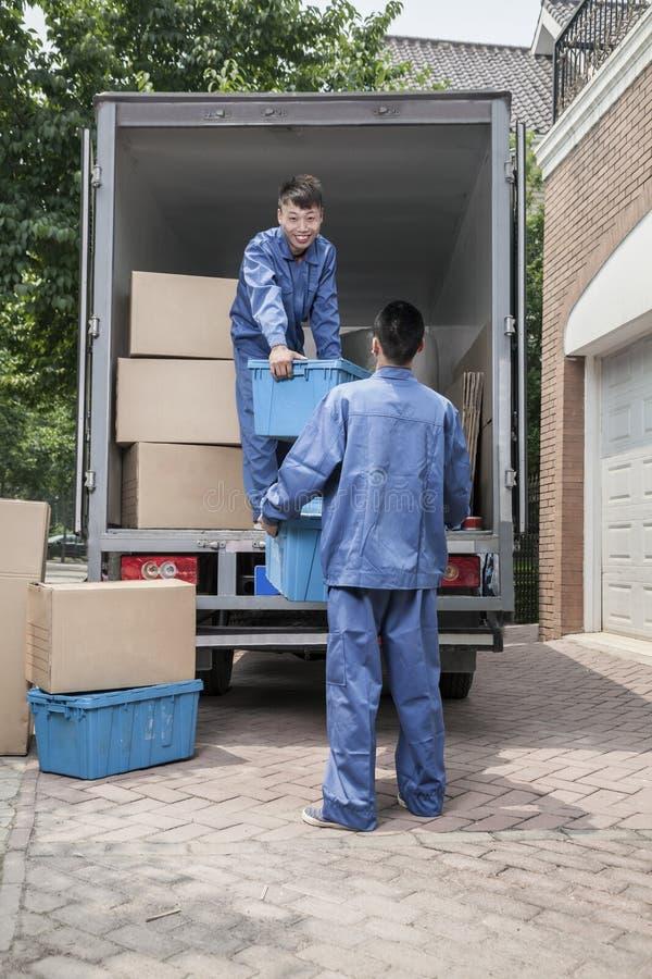 卸载一辆移动货车的搬家工人,通过纸板箱 库存照片