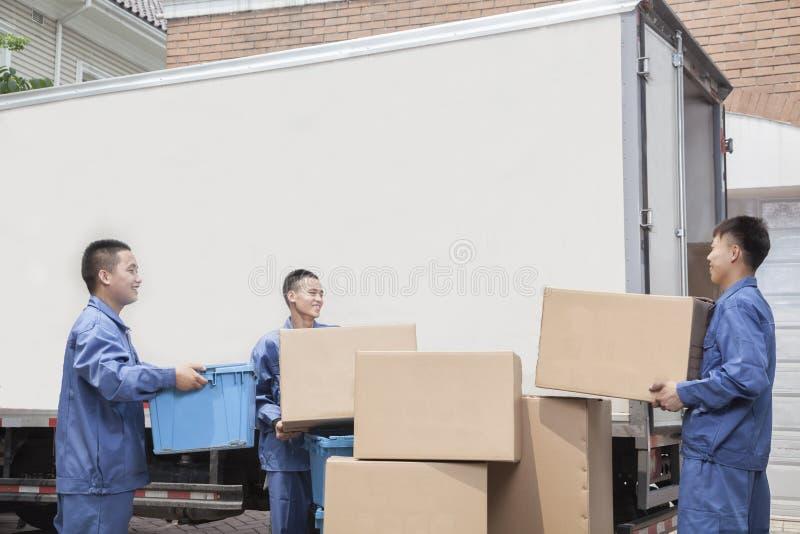 卸载一辆移动货车,许多被堆积的纸板箱的搬家工人 库存照片