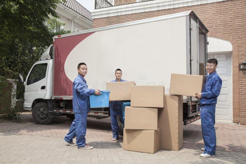 卸载一辆移动货车,许多被堆积的纸板箱的搬家工人 免版税库存照片