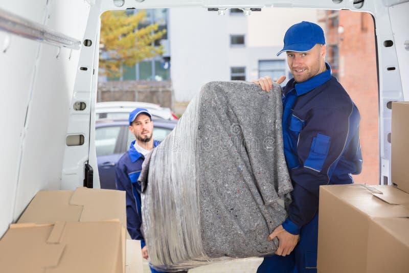 卸载从卡车的两名搬家工人家具 库存图片