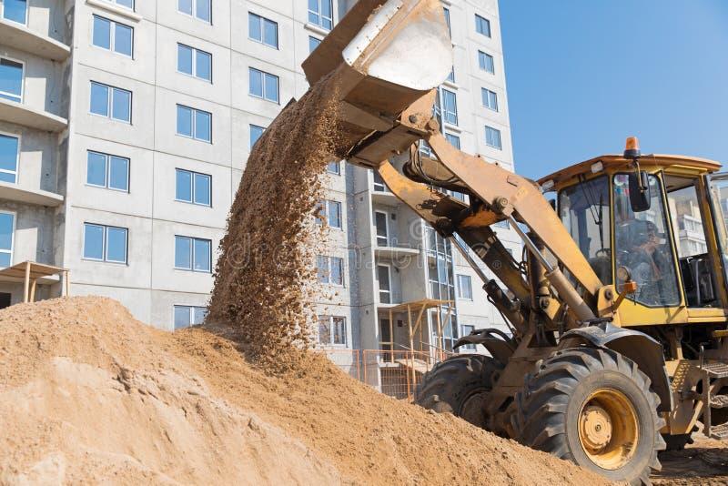 卸载从挖掘机桶的轮子装载者沙子 免版税库存照片