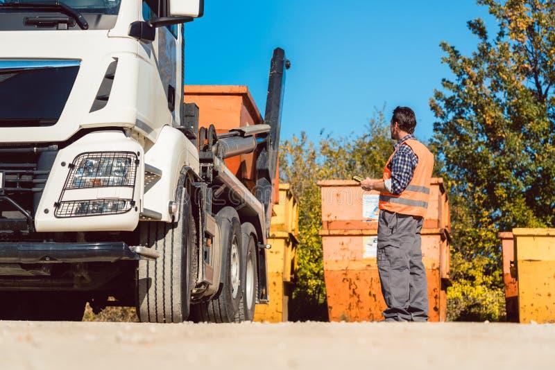 卸载废物的建造场所的工作者容器从卡车 库存照片