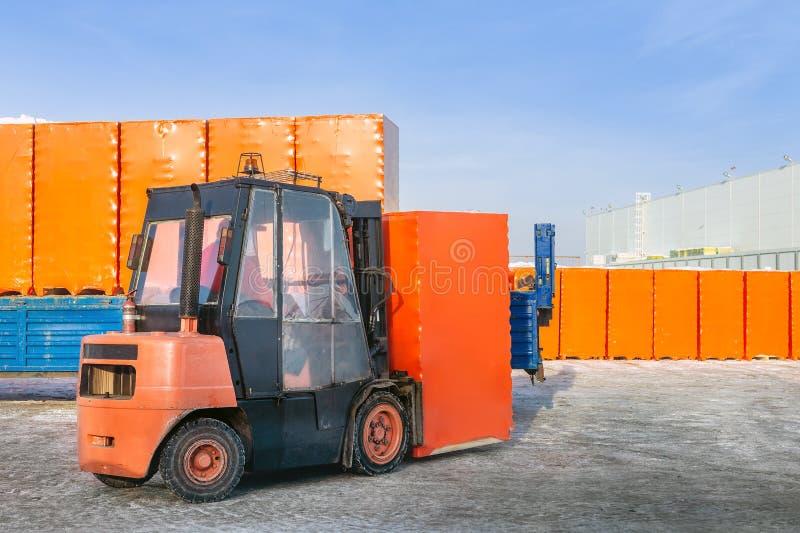 卸载有被包裹的纸板箱的铲车卡车半拖车户外 露天仓库运作背景 免版税库存图片