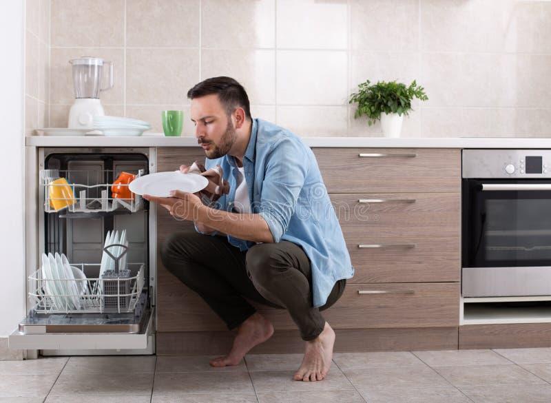 卸载洗碗机的人 免版税库存图片