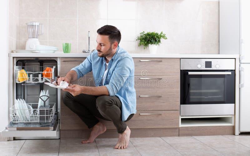 卸载洗碗机的人 免版税库存照片