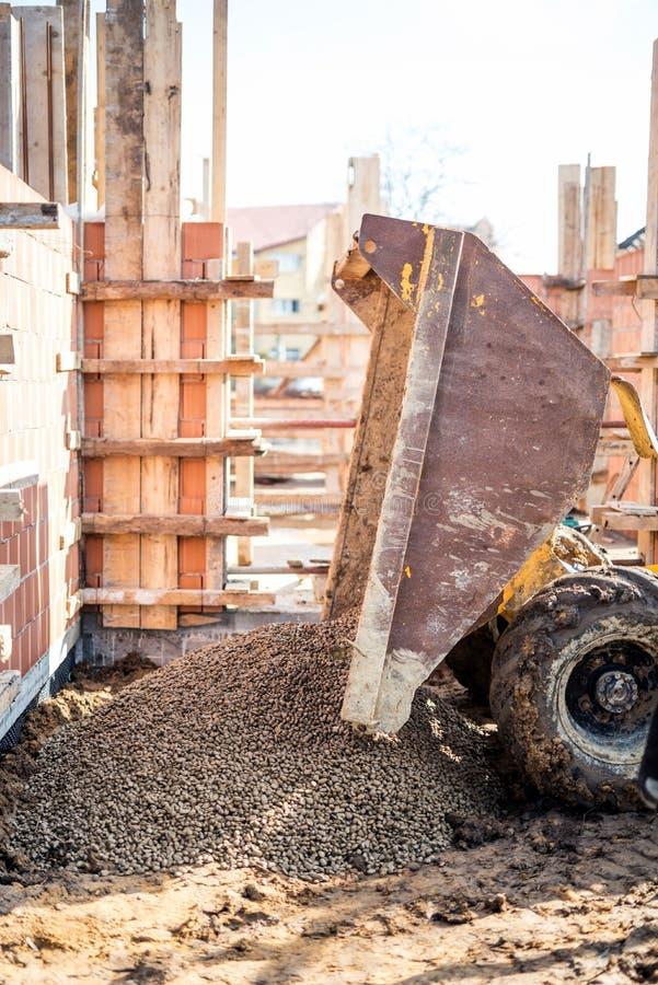 卸载建筑石渣、花岗岩和被击碎的石头的倾销者卡车在大厦基础 库存照片