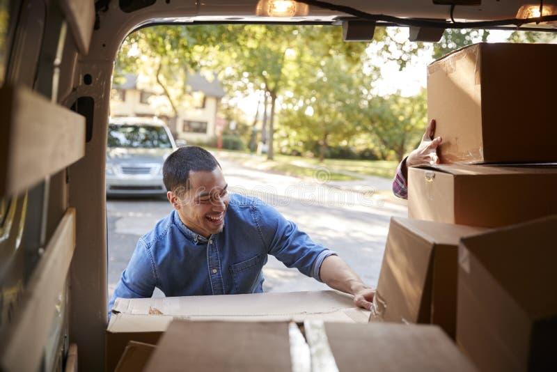 卸载Boxes From范On Family的夫妇移动在天 免版税图库摄影