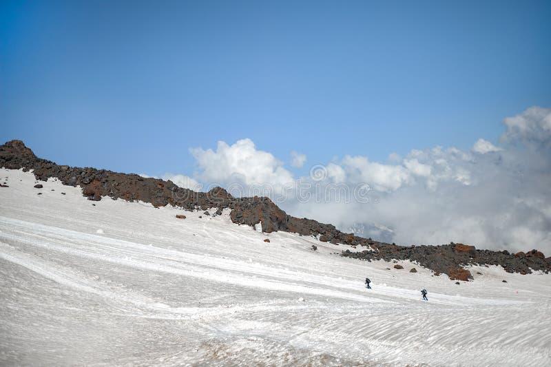 厄尔布鲁士峰倾斜-两个登山人在与背包的上面上升 免版税库存照片