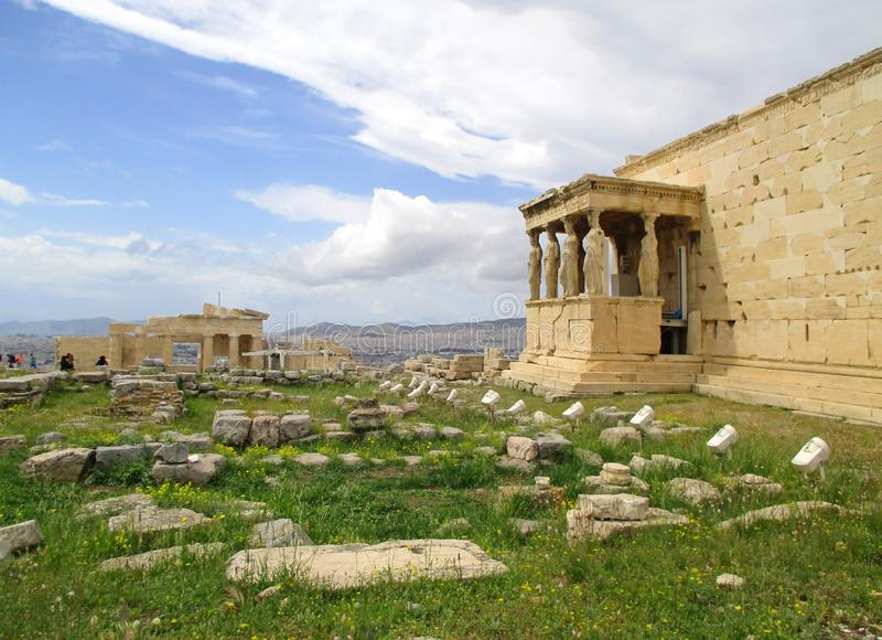 厄瑞克忒翁神庙古希腊寺庙门廊的女象柱专栏有Propylaea巨大的门的在距离,希腊 免版税库存照片