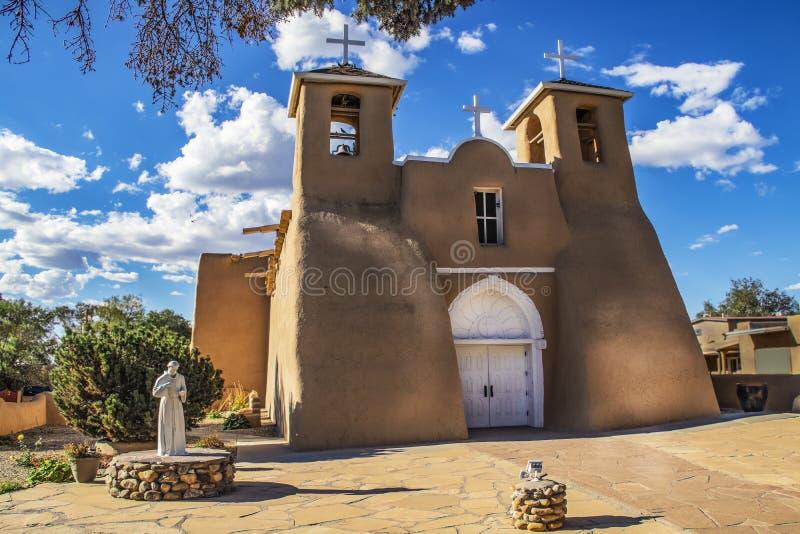 历史的多孔黏土旧金山de阿西西使命教会在剧烈的黄昏光的Taos新墨西哥在强烈的蓝天机智下 免版税库存图片