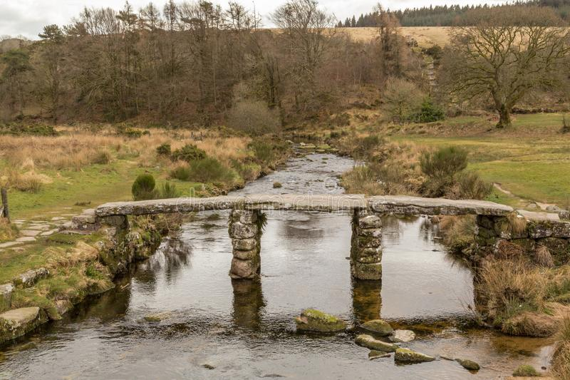 历史的拍板桥梁由花岗岩和穿过东方箭河做成在达特穆尔国立公园,英国 库存图片
