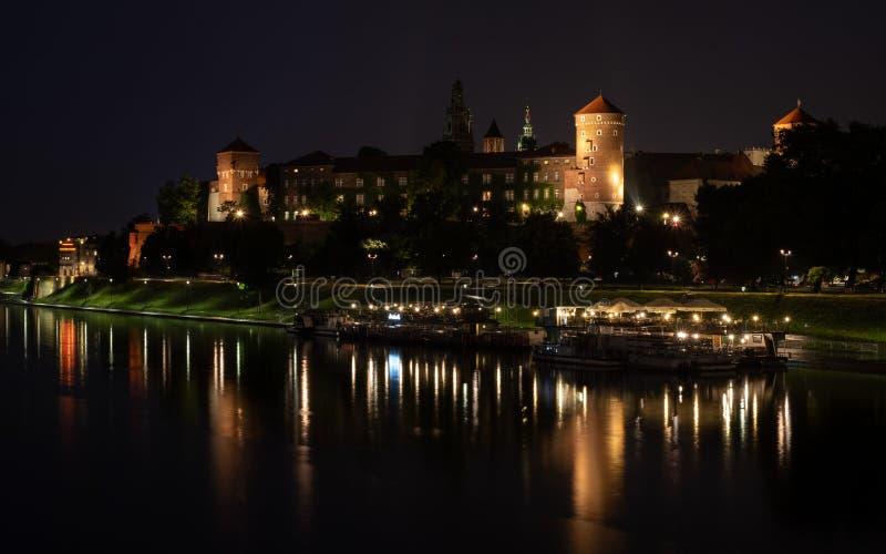 历史的瓦维尔山城堡在克拉科夫中部,波兰,被拍摄从维斯瓦河在晚上 免版税库存照片