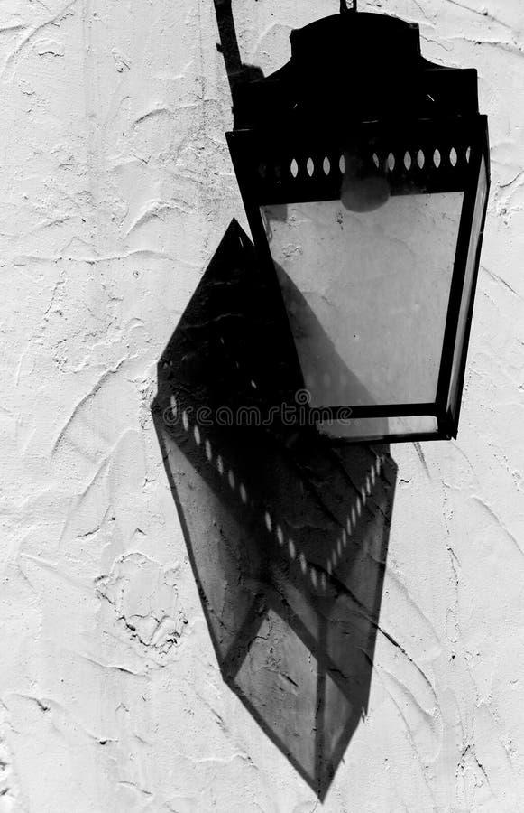 历史的路灯柱和阴影在墙壁上 免版税库存图片